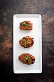 Tandoori beef tikka on a serving platter against a dark background