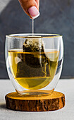 Woman hands hold of green tea bag in double glass cup