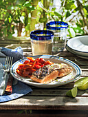 Grilled salmon with red pepper on an outdoor table