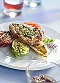 Pork steak on grilled salad hearts