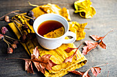 Cup of tea with lemon and dry leaves on wooden table