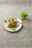 Hasselback potato with olives, basil paste and mozzarella cheese