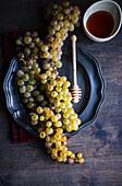 Weiße Trauben, Honiglöffel und Honig im Schälchen