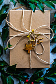 Rustic gift box decorated with fresh holly berry plant on concrete background