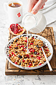 Granola with pomegranate and pouring milk