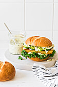 Fish burger with kale, cucumber and chimichurri mayonnaise sauce