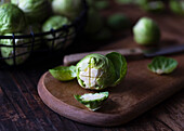 A brussel sprout on a wooden cutting board (Close up)
