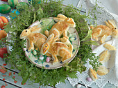 Easter bunnies made of puff pastry, in a salad wreath of mizuna and leaf mustard