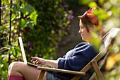 Woman using laptop in sunny summer garden