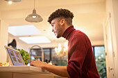 Young man working from home on laptop in kitchen