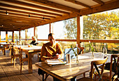 Businessman using smart phone in sunny autumn cafe