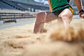 Female long jumper landing in sand