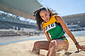 Female track and field athlete long jumping in sand