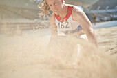Female track and field athlete landing in long jump sand