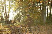 Happy woman bike riding among autumn leaves in sunny park