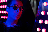 Young man in sunglasses in neon lighting
