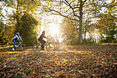 Couple riding bicycles in autumn leaves in sunny park