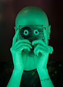 Woman with shaved head holding cassette tape in green light