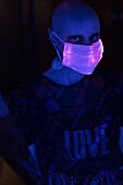 Woman with shaved head in iridescent face mask in dark