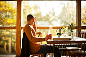 Businessman with hot coffee working at table in cafe
