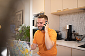 Happy young man working from home talking on smart phone