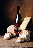Selection of cheeses with bottle and glass of red wine