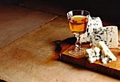 Roquefort mit einem Glas Weisswein auf Holzbrett