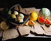 Verschiedene Melonensorten im Korb und auf Steinplatten
