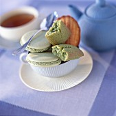 Macaroons, sponge finger cakes and Madeleine shell sponge cakes with tea