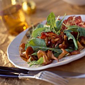 Chanterelle salad with spinach leaves and grilled coppa