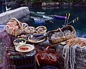 Verschiedene Meeresfrüchte und Krustentiere auf einer Steinmauer im Fischerhafen