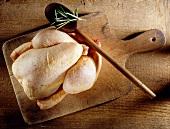 Ein rohes Hähnchen mit Rosmarin und Kochlöffel auf einem Holzbrett