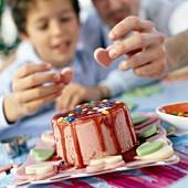 Mann und Kind verzieren eine Eistorte