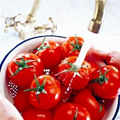 Tomatoes under running tap
