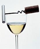 Ein Glas Weisswein mit Korkenzieher vor weißem Hintergrund