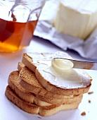 Zwieback mit Butter bestreichen
