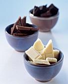 Broken bars of plain, dark and white chocolate in bowls