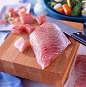 Raw fillet of perch on chopping board with knife