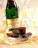 Champagner in Flasche und Gläsern mit Schokolade auf Teller