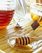 Honiglöffel neben Honigtopf, Teetasse im Hintergrund
