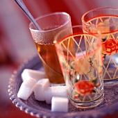 Drei bunte Gläser, eines davon mit heißem Minztee mit Zuckerwürfeln auf einem Tablett
