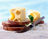 Cubes of Emmental cheese with slices of bread and knife
