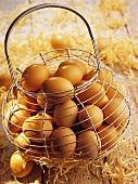 Drahtkorb mit braunen Hühnereiern und Holzwolle