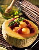 Melonenbällchen und Himbeeren in ausgehöhlter Melone