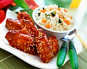 Glazed chicken wings with sesame seeds and bowl of rice