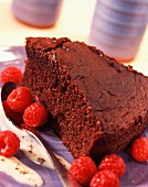 Slice of moist chocolate cake with raspberries
