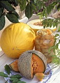 Saures Melonenkompott im Glas und frische Melonen daneben