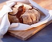 Ein Brotlaib in eine weisse Stoffserviette gewickelt
