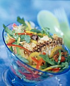 Warm fish salad with peppers, sesame seeds and tomato