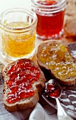Slices of bread and jam with jars of jam